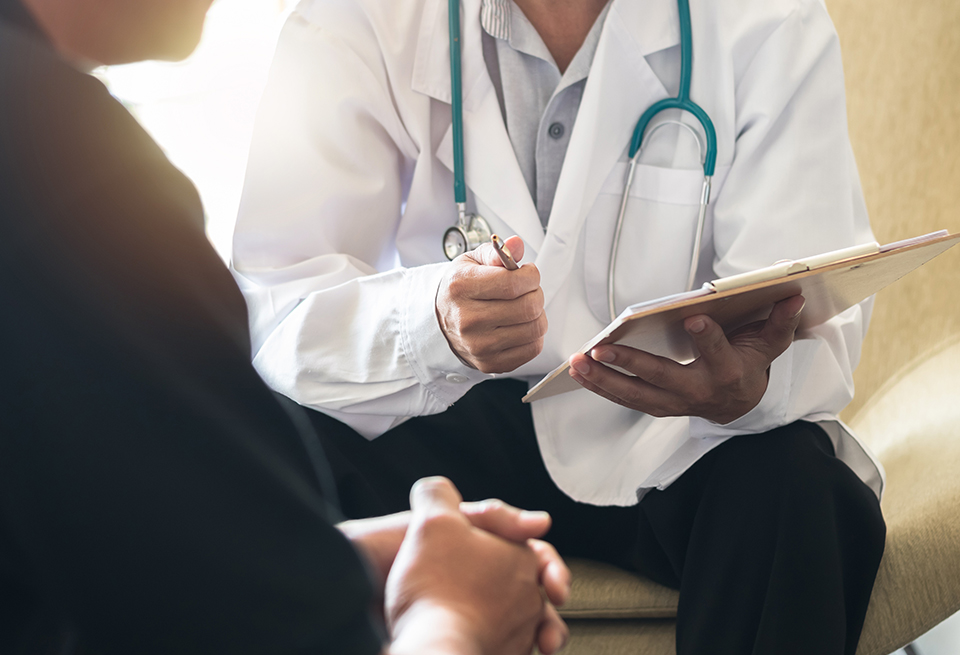 A physician with a pen and clipboard discusses treatment with a male patient.